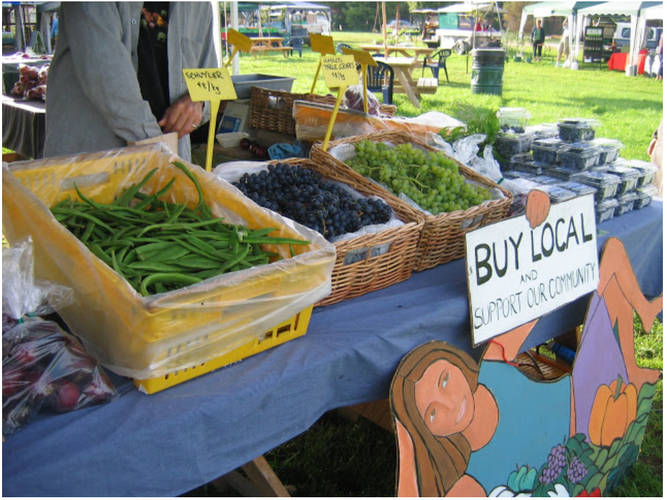 Buy local food sign at farmers market stall displaying homegrown grapes berries and veges
