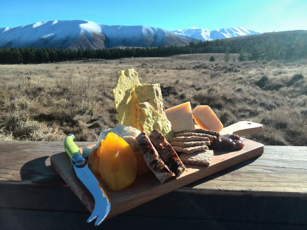 Delicious artisan cheese platter served on wooden board with scenic snow capped mountains in background
